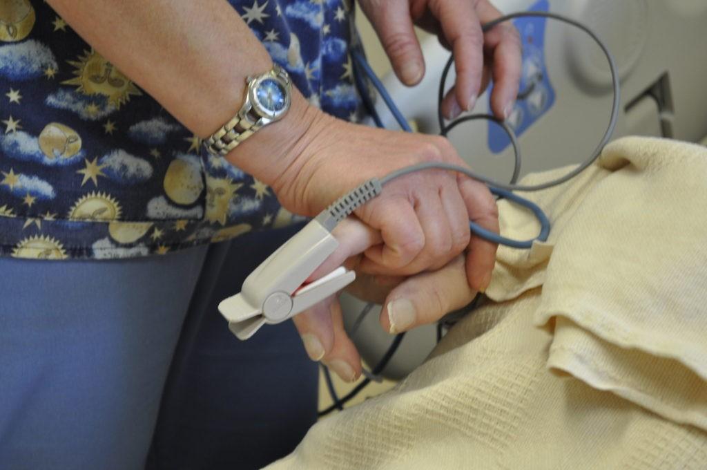 CCU nurse holding patient hand