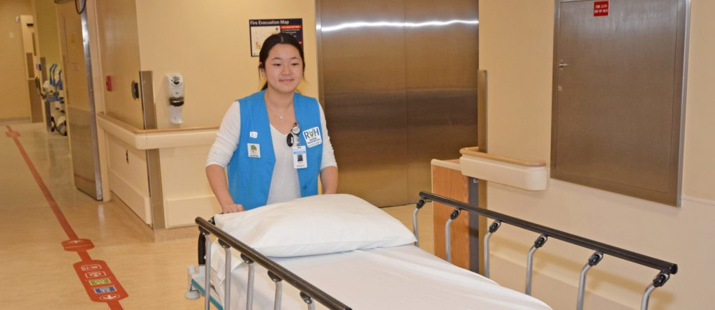 Student volunteer moving a patient bed